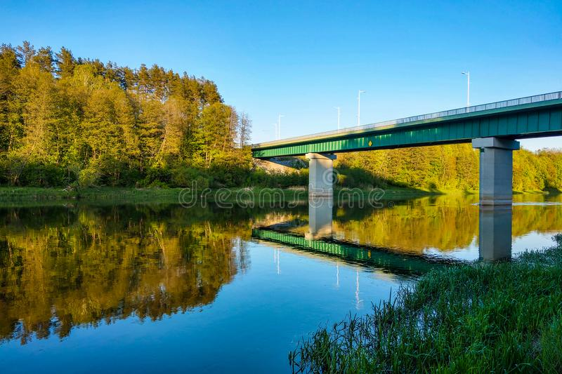 Beautiful river with a forest, the reflection of trees in the water, smooth calm surface of the water without waves royalty free stock photos