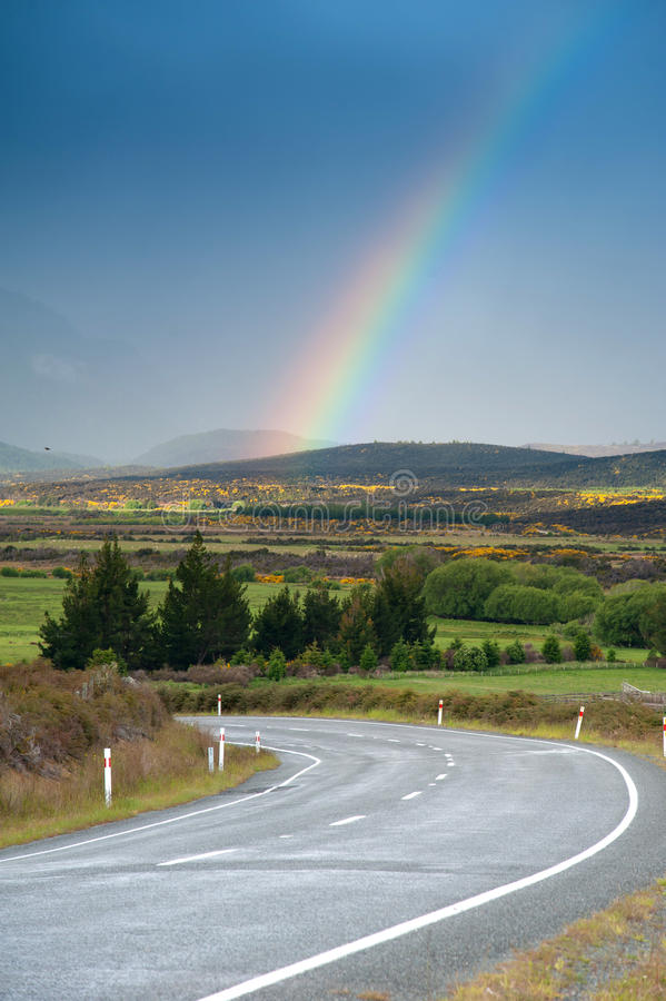 Beautiful road with rainbow in blue sky, South Island, New Zealand royalty free stock photography