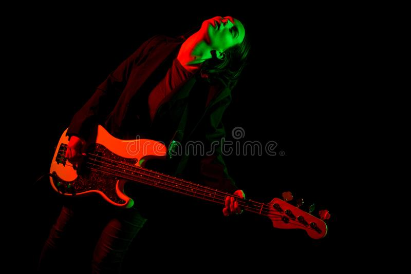 Beautiful rock girl playing bass guitar royalty free stock images