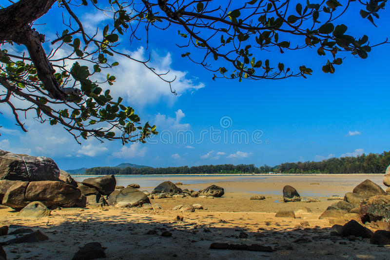 Beautiful rock stones on the beach when the sea water receded wi. Th dramatic blue sky background on the cloudy day stock image