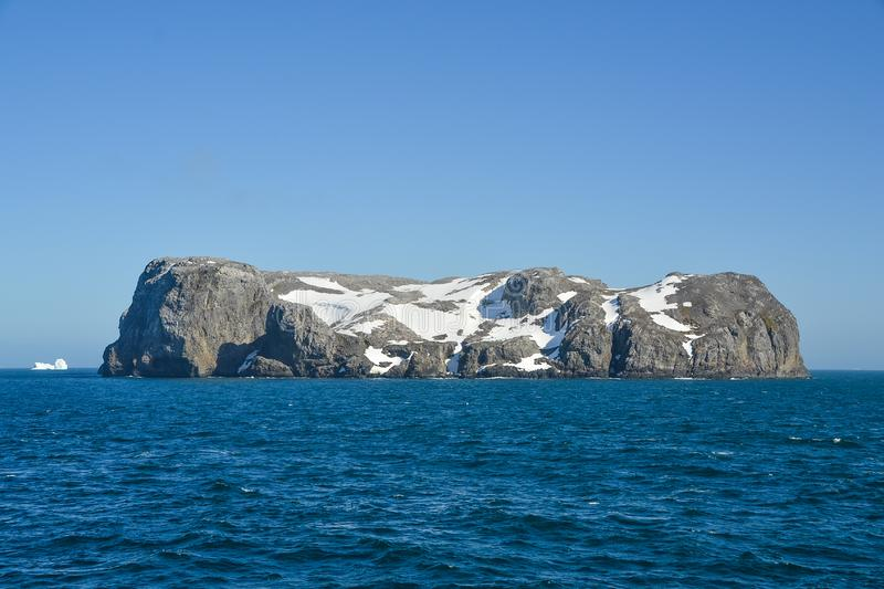 Snowy rocky island. A beautiful rocky island in the middle of Antarctic waters covered in snow stock images