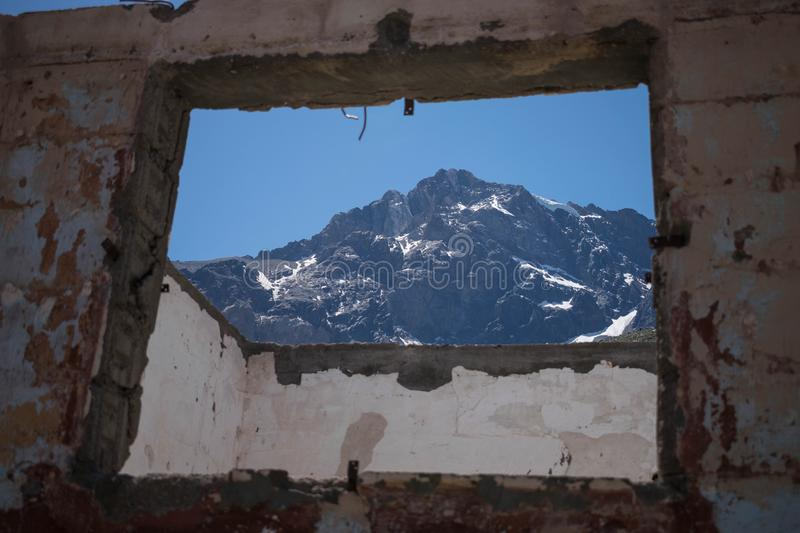 Beautiful rocky mountain seen through a square shaped opening from a stone building. A beautiful rocky mountain seen through a square shaped opening from a stone stock image