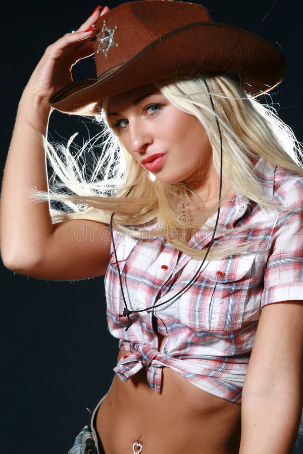 Beautiful rodeo girl wearing a cowboy hat. On pink background royalty free stock photography