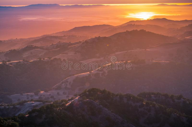 Beautiful rolling hills bathed in the sunset light; the setting sun reflected in the water of the San Francisco Bay in the royalty free stock photography