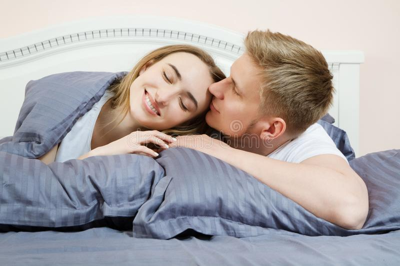 Beautiful romantic couple in bed, happy relationship, heterosexual couple.  royalty free stock photography