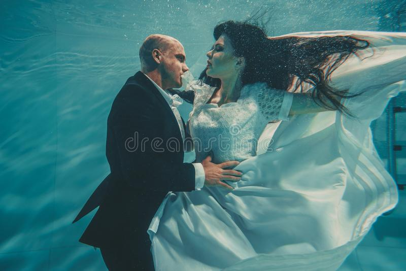 Beautiful romantic couple of bride and groom after wedding swimming gently under water and relax stock photo