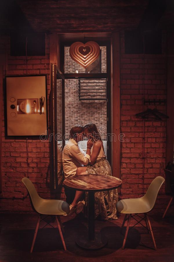 Beautiful romantic couple dating in cafe. Young lovers hugging and kissing at table. Authentic Love date stock photos