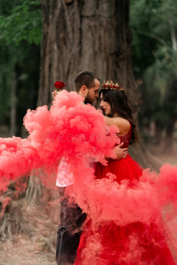 Beautiful romantic couple kiss closeup. Attractive young woman in red dress and crown with handsome man in white shirt are in love. Beautiful romantic couple on stock photography
