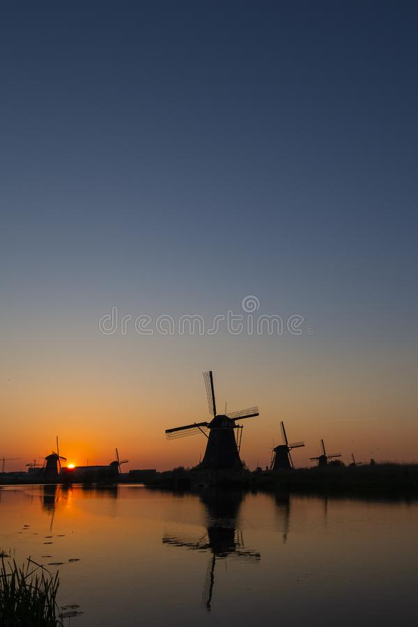 Beautiful Romantic Dutch Windmills in Front of The River in Kinderdijk Village in the Netherlands. Picture Taken At Golden Hour. Vertical Shot royalty free stock photography