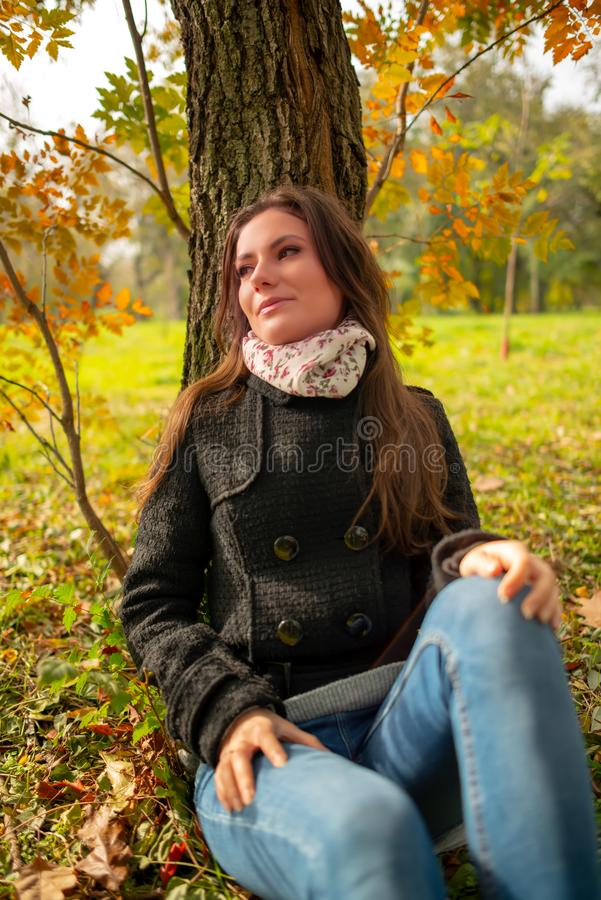 Beautiful romantic girl in a park autumn scenery, sitting down and leaning against a tree, enjoying the warm sunny day stock photo