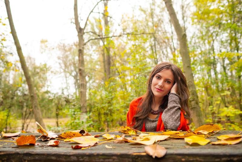 Beautiful romantic girl in park autumn scenery, sitting down at a wooden table covered with yellow leaves, looking at royalty free stock images