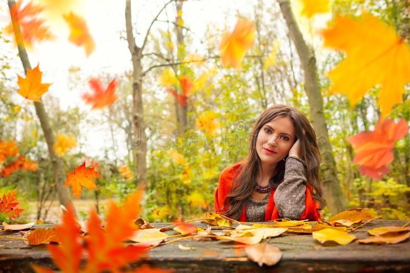 Beautiful romantic girl in park autumn scenery, sitting down at a wooden table and looking at the camera, blurred yellow royalty free stock images