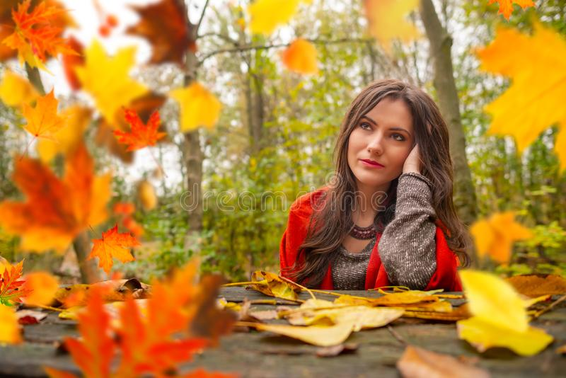 Beautiful romantic girl in park autumn scenery, sitting down at a wooden table and looking up, blurred yellow leaves are stock images