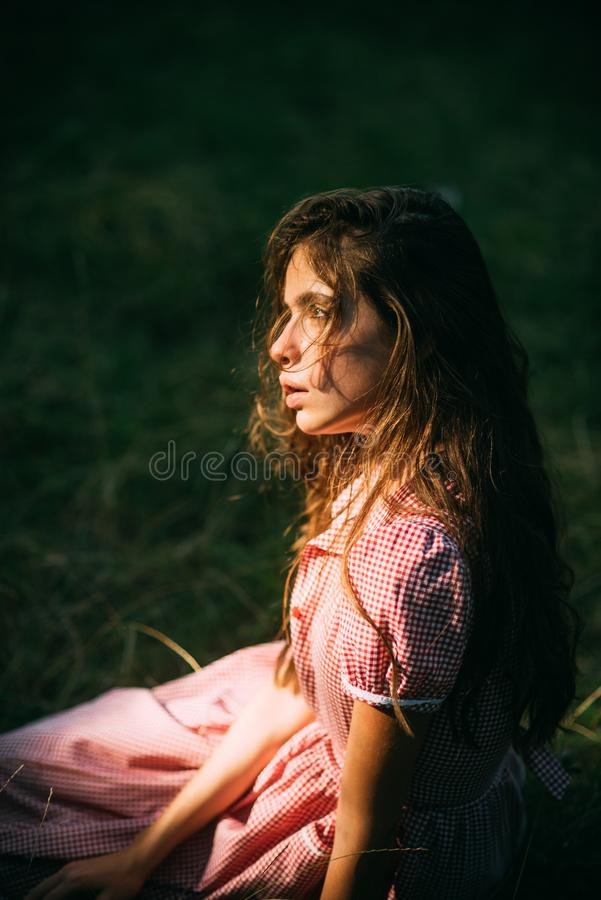 Beautiful romantic girl in vintage dress on sunny meadow. Side view dreamy young woman with curly hair sitting on grass stock image
