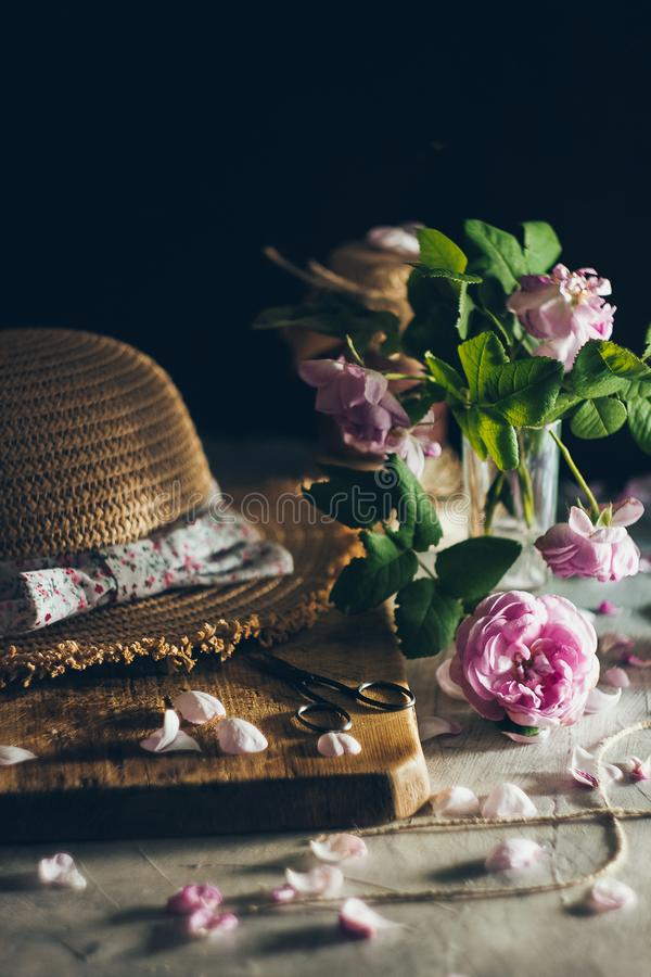 A beautiful romantic lifestyle composition with straw hat and roses petals on the wooden and rustic background. A beautiful romantic lifestyle composition with a royalty free stock photo