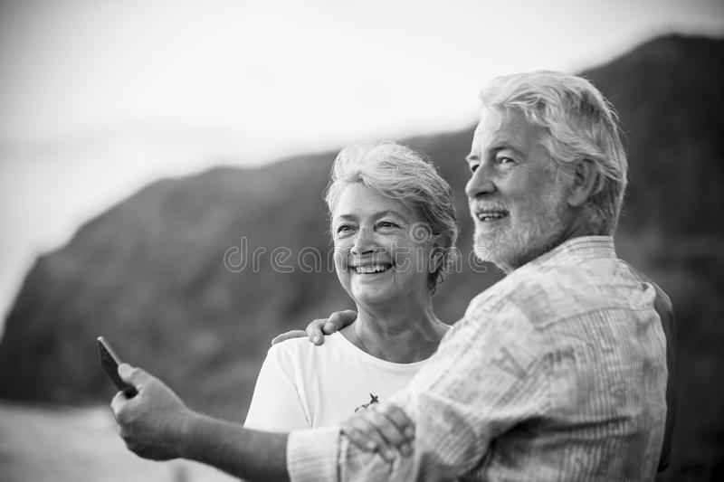 Beautiful romantic portrait of senior happy couple smile and hug eachother with love - forever together concept and active elderly royalty free stock image