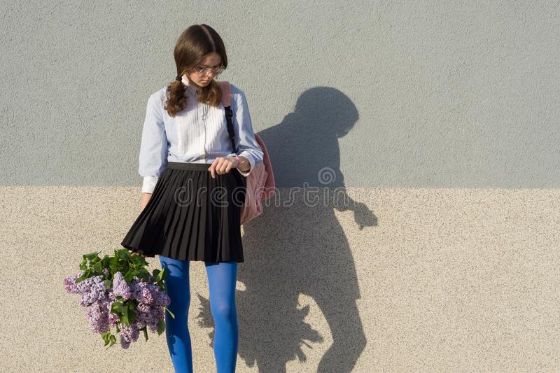 Beautiful romantic teenage girl look at watch, with bouquet of lilac on gray wall background, copy space.  stock photo