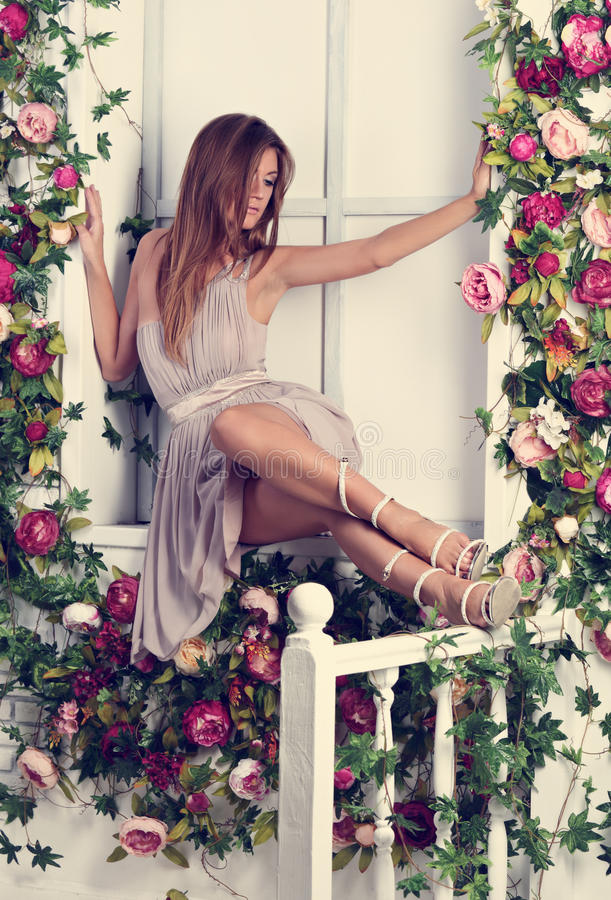 Beautiful romantic thinking woman with long hair sitting and posing on the window sill in fashion summer dress and trendy shoes i stock images