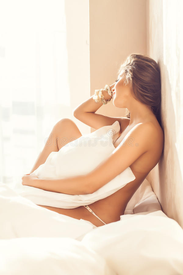 Beautiful romantic woman / girl brunette lying on the bed in her room at home. stock photos