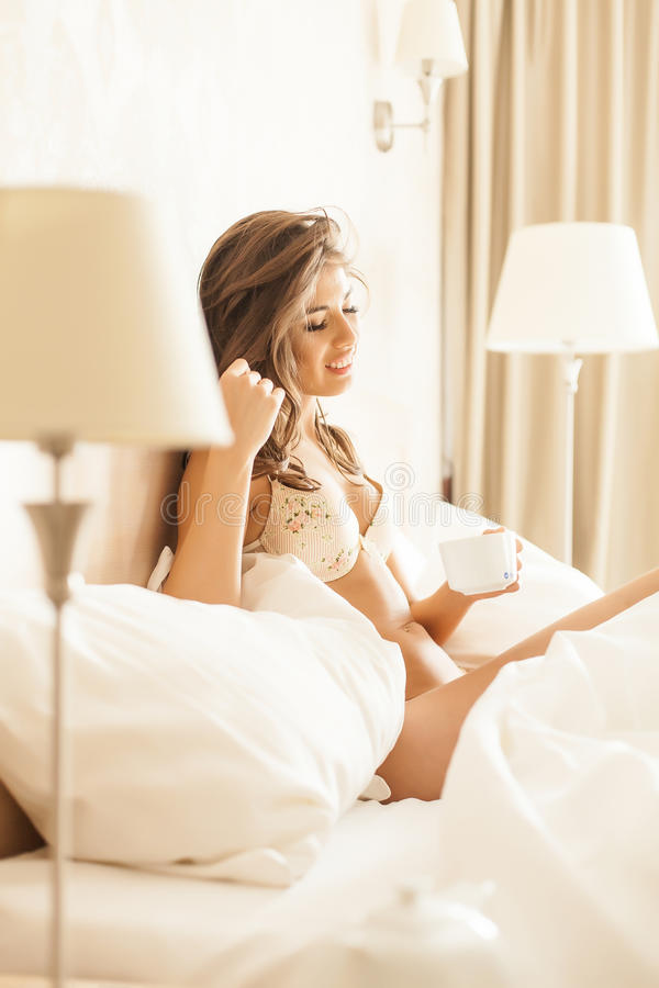 Beautiful romantic woman / girl brunette lying on the bed in her room at home. stock photography
