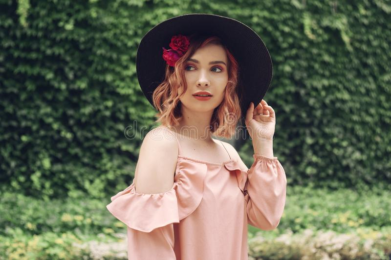 Beautiful romantic young woman on a background of natural  green wall of plants posing with flowers in head hair. Summer vibes. royalty free stock photo