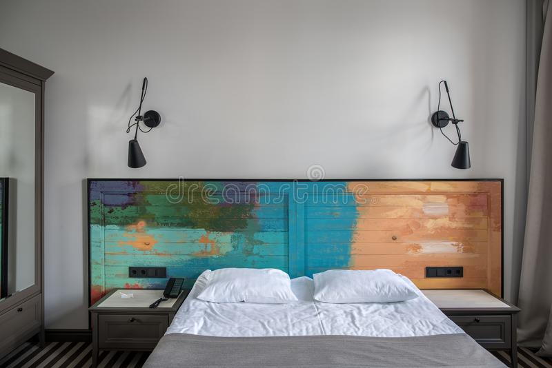 Stylish hotel room. Beautiful room in a hotel with light walls and striped floor. There is a blue double bed with a colorful wooden bedhead, dark gray stock photography