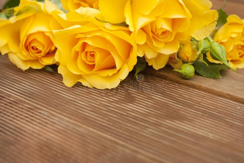 Beautiful Roses Bouquet over Wooden Table. Copy Space. Vintage yeelow flowers. stock photos