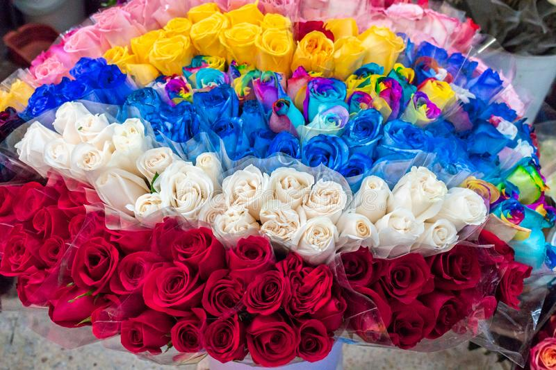 Group of roses of various colors arranged in a bowl. Beautiful roses, flowers of varied colors in bouquets arranged for sale in a market stall royalty free stock photos