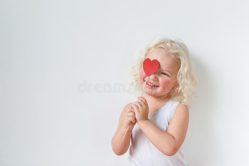 Beautiful rouge smiling happy female child covers face with heart stick, has pleasant smile, isolated over white royalty free stock photo