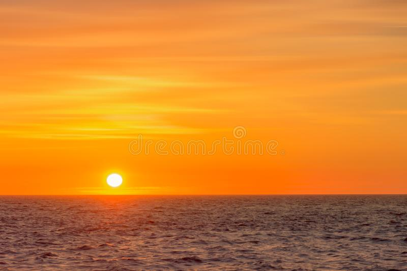 Beautiful round and bright sun setting against a vivid orange sk. Y with high altitude tin clouds over the horizon of the North sea royalty free stock image