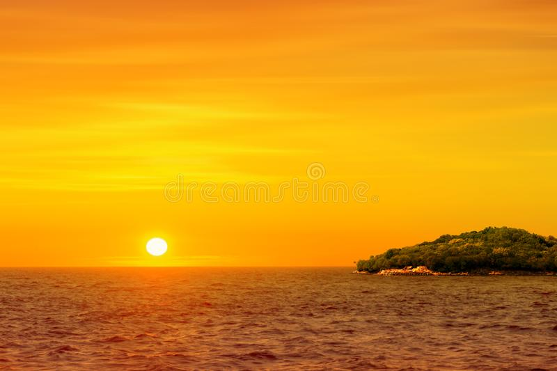 Beautiful round and bright sun setting against a vivid orange sk royalty free stock images