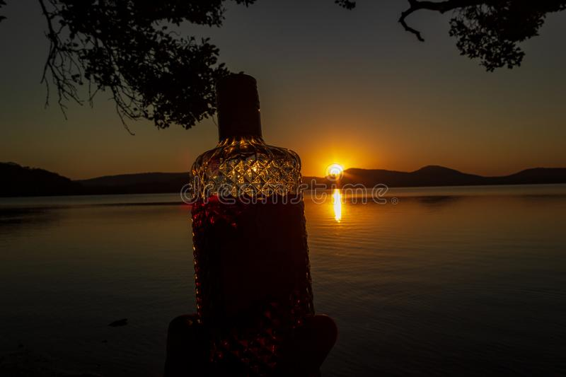 beautiful rum bottle full with rum holding in front of a sunset over Watson Taylors Lake at Crowdy Bay National Park, New South stock photos