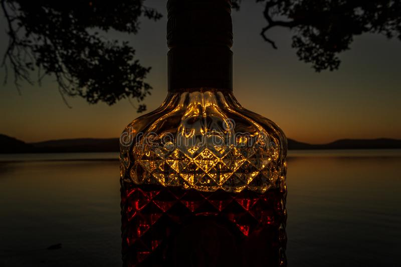 beautiful rum bottle full with rum holding in front of a sunset over Watson Taylors Lake at Crowdy Bay National Park, New South royalty free stock image