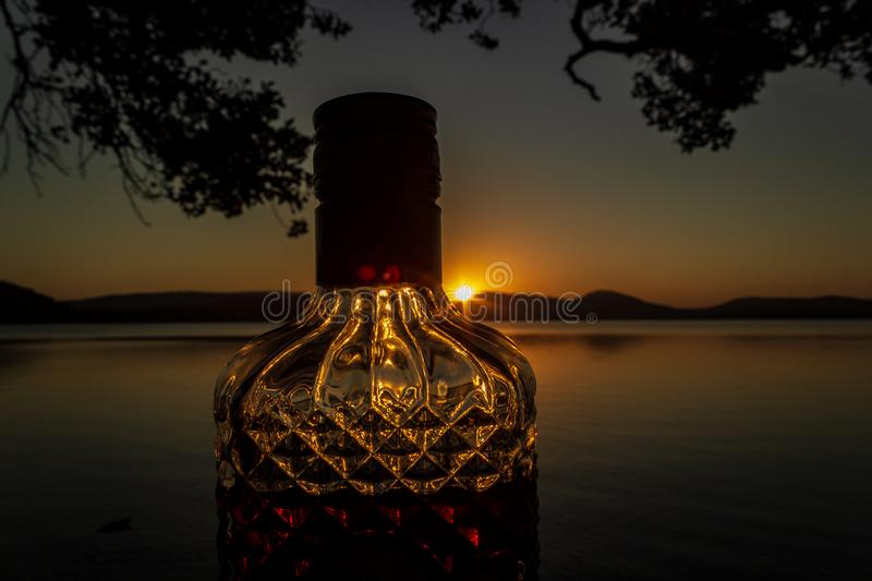 beautiful rum bottle full with rum holding in front of a sunset over Watson Taylors Lake at Crowdy Bay National Park, New South stock photography