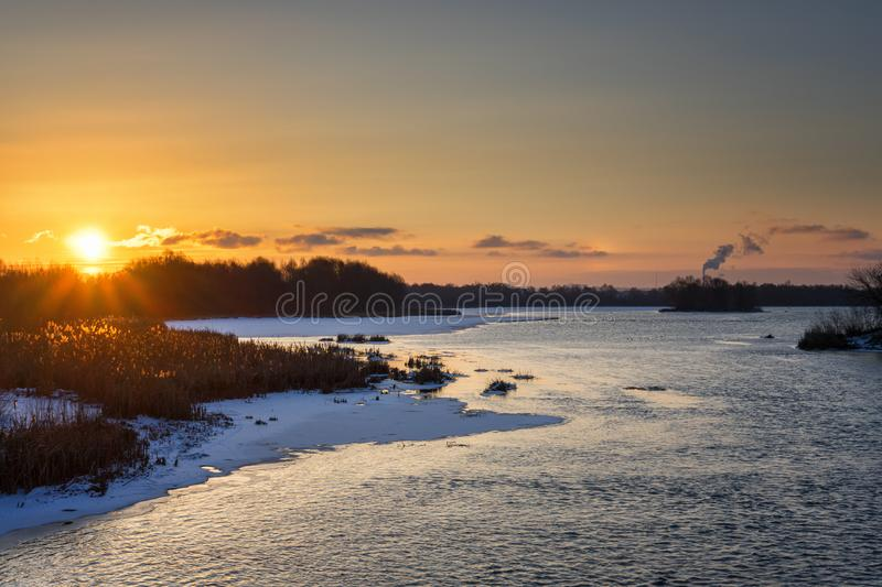 Beautiful russian early winter landscape with non frozen river, snow-covered riverside and dried grass at sunset. Scenic nature royalty free stock image