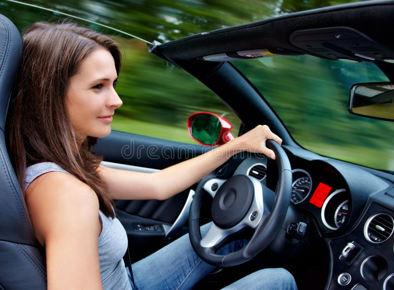 Beautiful 20s driving a roadster. Beautiful 20s girl driving a roadster stock photo