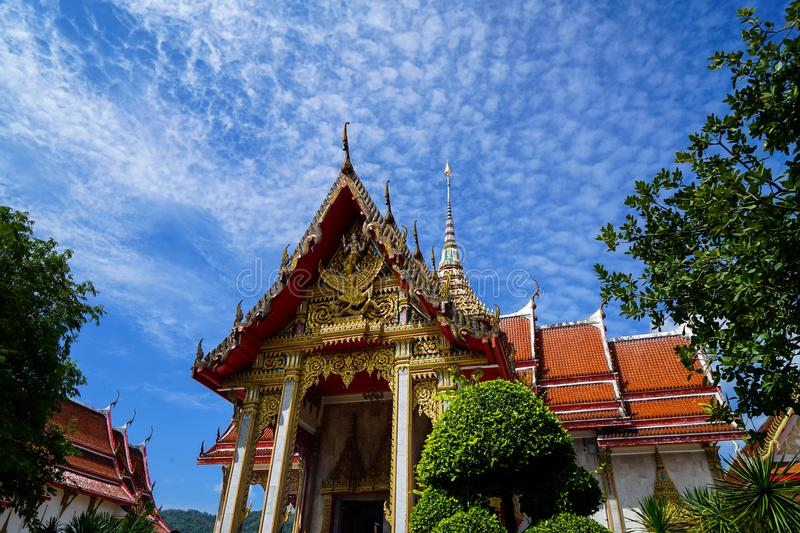 Beautiful sacred red roof and golden spire ornament main hall of famous buddhist temple landscape with blue sky and white cloud royalty free stock photos