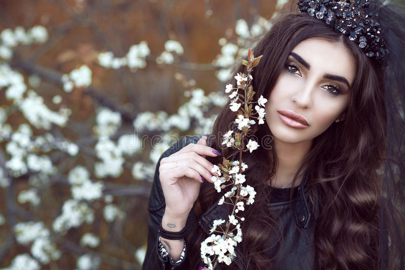 Beautiful sad dark-haired young woman with perfect make up wearing black jewel crown with veil holding blossomed half faded branch royalty free stock image