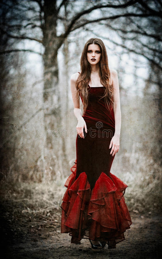Beautiful sad girl in the autumnal forest. Grunge texture effect stock photo