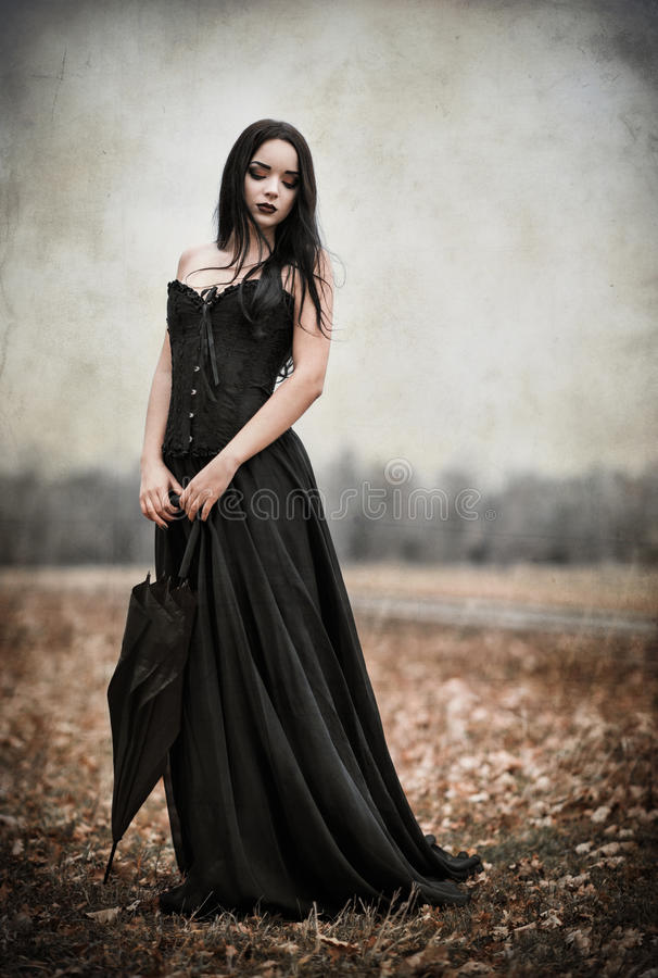 Beautiful sad goth girl holds black umbrella. Grunge texture effect stock photography
