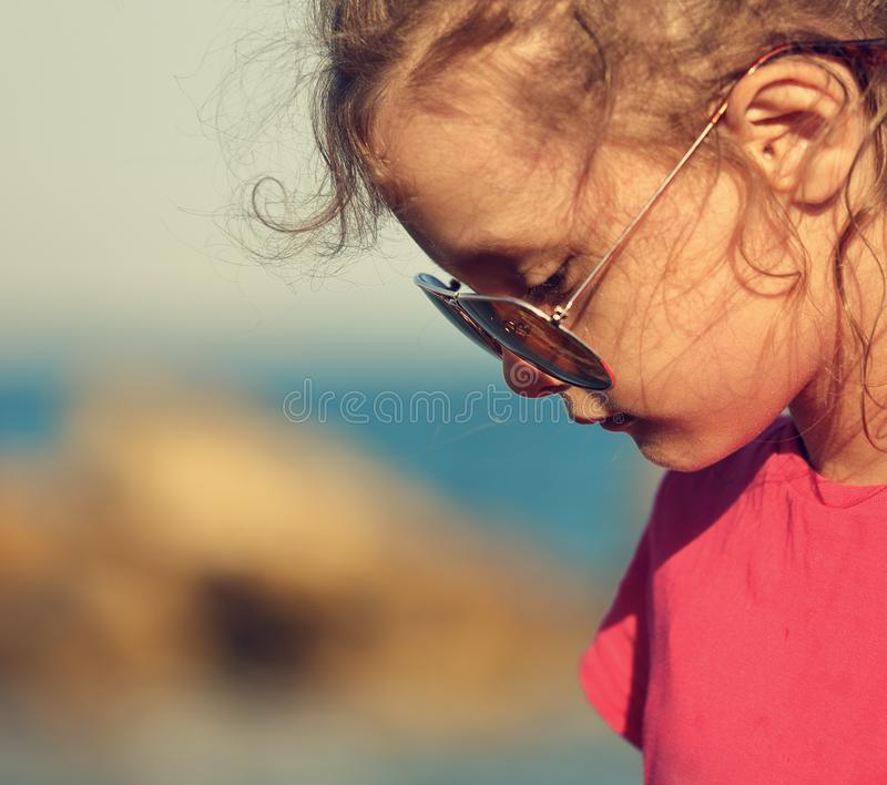 Beautiful sad kid girl profile in fashion trendy sunglasses walk royalty free stock images
