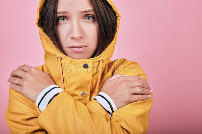 Beautiful sad lady with green eyes in yellow raincoat is frozen stock photography