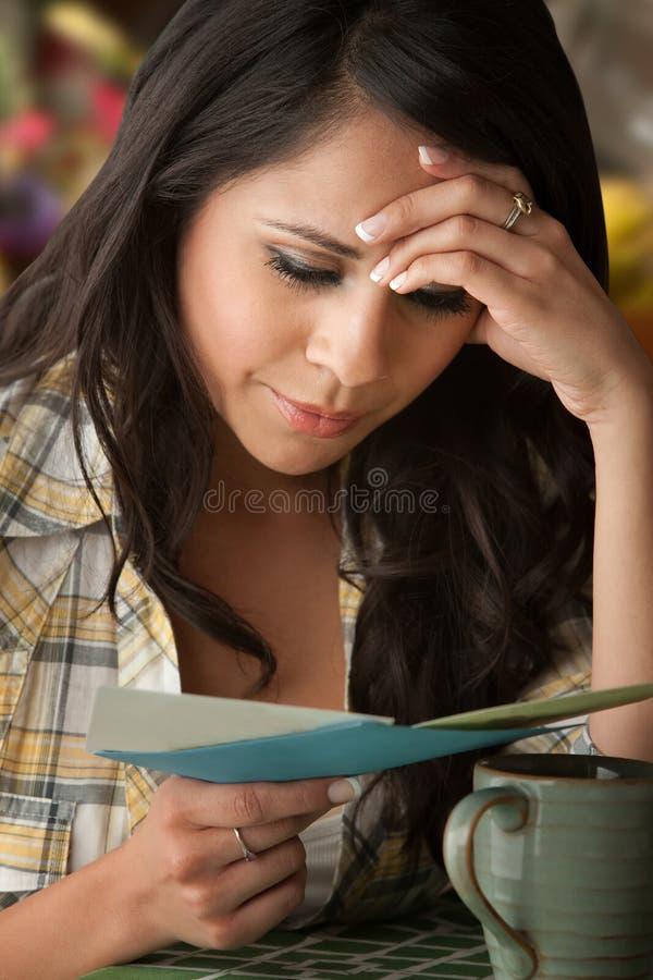 Beautiful Sad Latina Woman with Sympathy Card. Beautiful Serious Latina Woman at Table in Kitchen Sympathy Card stock image