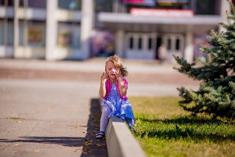 Beautiful sad little girl crying, on summer background. Cranky royalty free stock photos