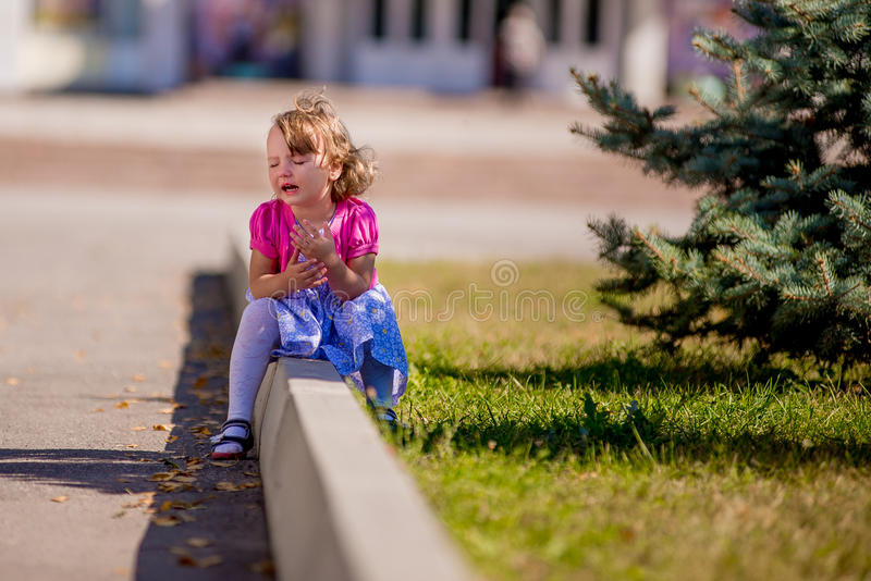 Beautiful sad little girl crying, on summer background. Cranky royalty free stock photography