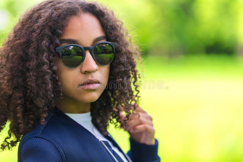 Mixed Race African American Girl Teen Sunglasses. A beautiful sad moody mixed race African American female girl teenager young woman in sunshine wearing royalty free stock photo