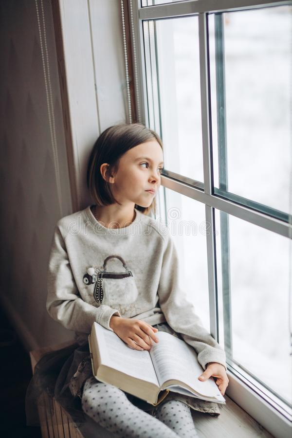 Beautiful sad unhappy girl looking at the window while resting on the windowsill. At home. sadness. girl wants to go for a walk instead of reading a book royalty free stock images
