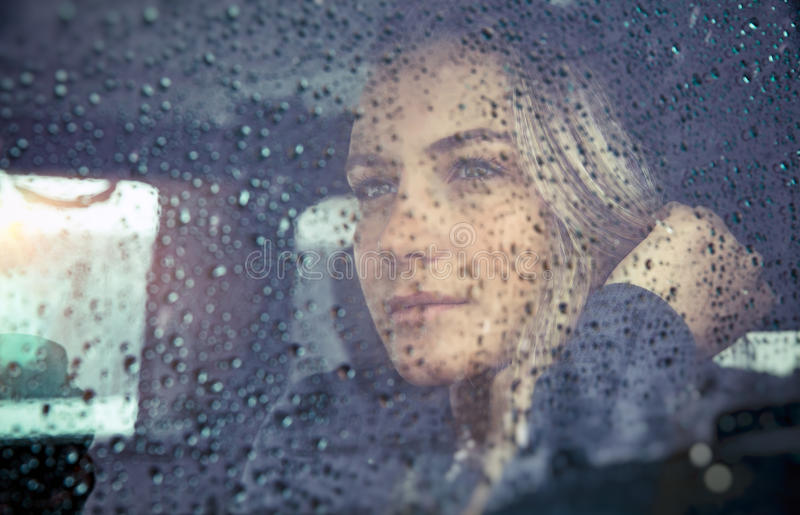 Beautiful sad woman in the car. Portrait of a beautiful sad woman sitting in the car in rainy weather, pensive girl looking through the window glass with rain stock images