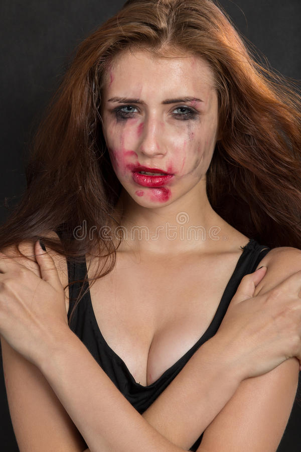 Beautiful sad woman. With smeared cosmetics on black background stock image