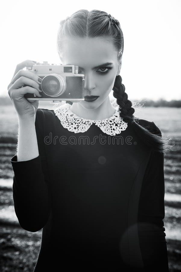 Beautiful sad young girl photographing on vintage film camera. Black and white stock image